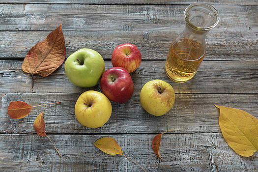 Apple cider in  bottle,  and fresh apples on wooden background by Julian Popov
