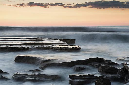 Beautiful dramatic Sunset over a rocky coast by Michalakis Ppalis