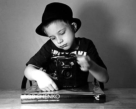 Boy in hat with old camera. by Mitchell Ozog