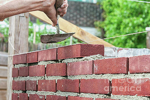 Bricklayer with trowel by Patricia Hofmeester