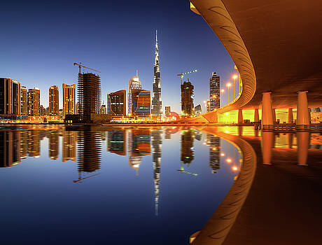 Fascinating reflection of tallest skyscrapers in Business Bay district during sunset. Dubai, United Arab Emirates. by Marek Kijevsky