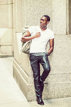 Alexander Image - Happy young African American man carrying shoulder bag, travelin