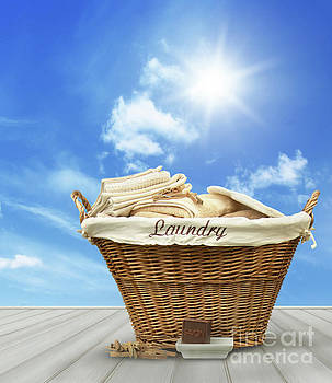 Sandra Cunningham - Laundry basket with clothes on rustic table against blue sky