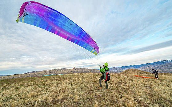 Patrick McFarland launching his paraglider on a hill near Horses by Elijah Weber