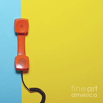 Retro orange telephone tube on striped blue and yellow backgroun by Aleksandar Mijatovic