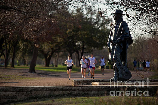 Herronstock Prints - Runners and joggers pass by the Stevie Ray Vaughan Memorial Statue on Lady Bird Town Lake hike and bike trail