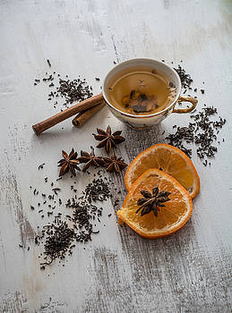 Tea, dried cinnamon,orange and anise on wooden background by Julian Popov