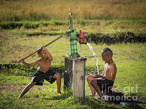 Two young boy rocking groundwater bathe in the hot days. by Tosporn Preede