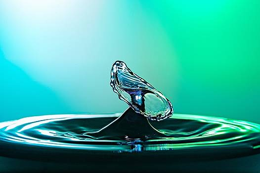 Water drop collision close up image with a green and blue background by Teemu Tretjakov
