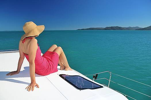 Woman in red dress on sailing catamaran in the Whitsundays. by Keiran Lusk