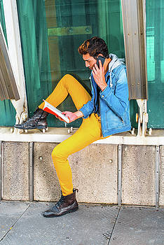 Alexander Image - Young man reading book, talking on cell phone outside in New Yor