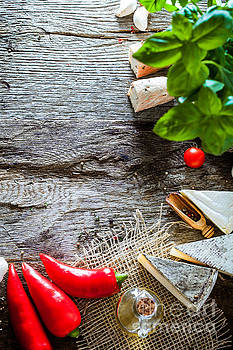 Pizza on wood with ingredients by Mythja Photography
