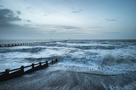 Beautiful dramatic stormy landscape image of waves crashing onto by Matthew Gibson