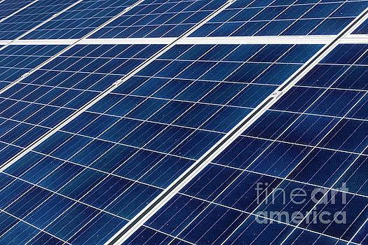Solar Panel Array Under A Blue Sky by Carl Chapman