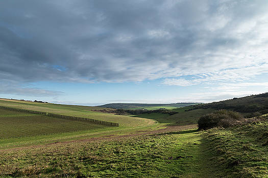Stunning English countryside landscape across rolling green hill by Matthew Gibson