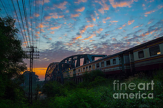 Train Passing by over Rural Railway Bridge in the Morning or at  by Thampapon Otavorn