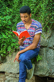 Alexander Image - Young African American Man reading book, traveling, relaxing at