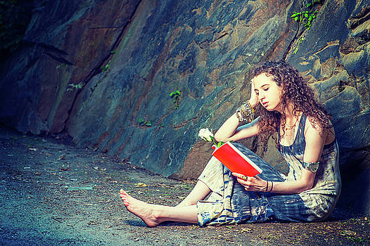 Alexander Image - Young American Woman reading red book, sitting on ground, travel