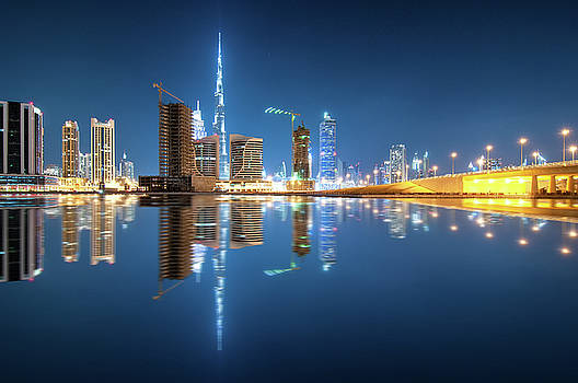 Fascinating reflection of tallest skyscrapers in Business Bay district during calm night. Dubai, United Arab Emirates. by Marek Kijevsky