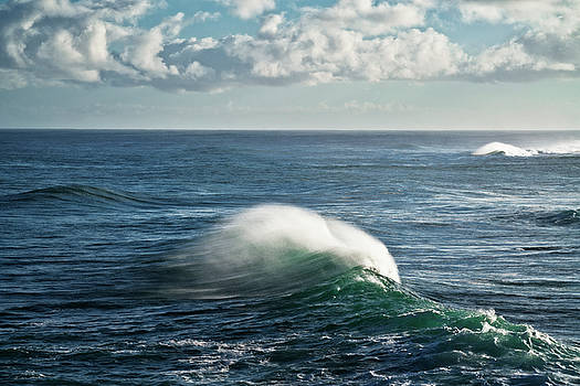 Large cresting waves with spindrift tails along the North Shore. by Larry Geddis