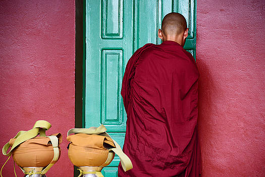 Young Cambodian Buddhist in red unlocked green door by Mirko Dabic