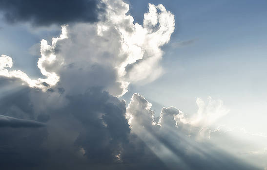 Cloudy sky with sun rays by Blink Images