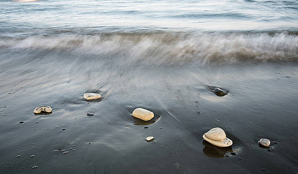 Pebbles in the beach and flowing sea water by Michalakis Ppalis