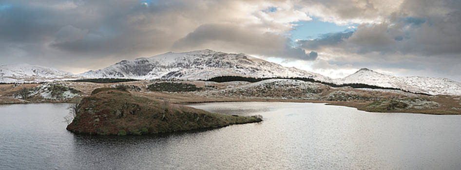 Beautiful long exposure Winter landscape image of Llyn y Dywarch by Matthew Gibson