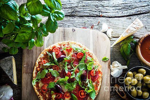 Fresh pizza on wood by Mythja Photography