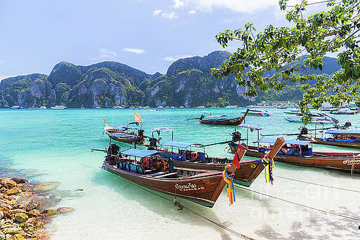 Long-tail boats, the Andaman Sea and hills in Ko Phi Phi Don, Th by Travel and Destinations - By Mike Clegg