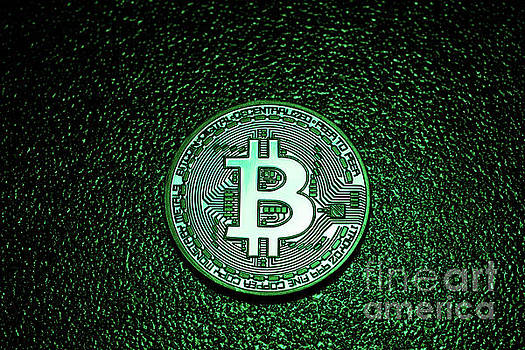 Michal Bednarek - A coin with bitcoin logo in a green lighting.