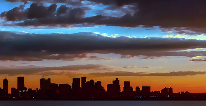 A dark Boston skyline against the orange and blue sky by Thomas Logan
