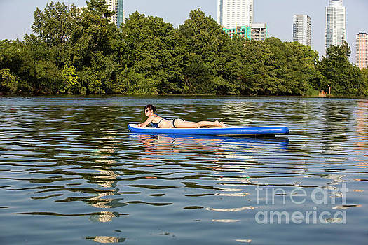 Herronstock Prints - A female stand up paddle board lounges on the crystal clear blue waters of on Lady Bird Lake in Austin, Texas- Stock Image