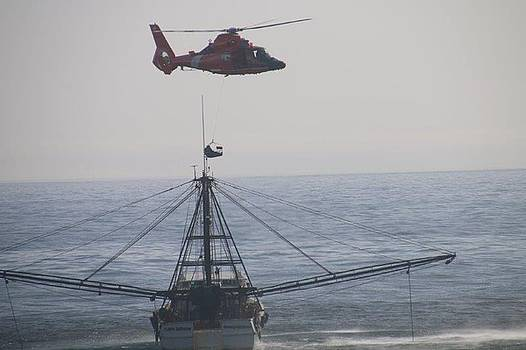 A helicopter hovers close to Capt Nathan trawler the coast guard medevaced the Captain by Paul Fearn