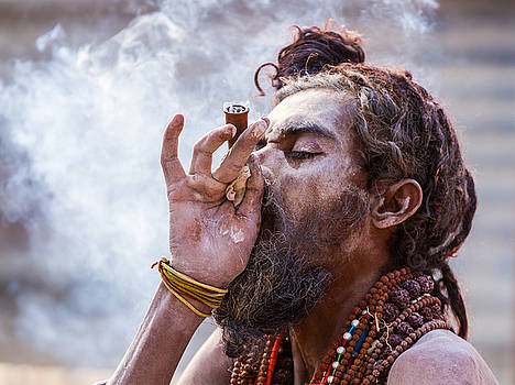 A Hindu sadhu smoking a hash pipe - India. by Nila Newsom