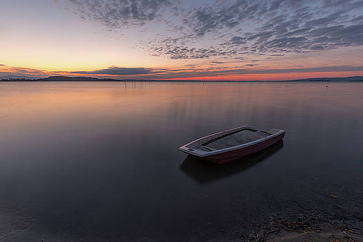 A little fishing boat in the middle of perfectly still water by Massimo Discepoli