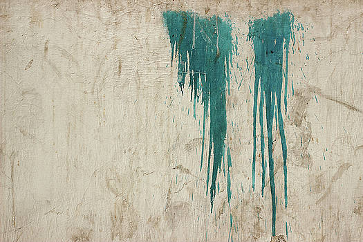 A minimalist photo of Two patches of dripping blue paint on a textured Indian wall by Prakash Ghai