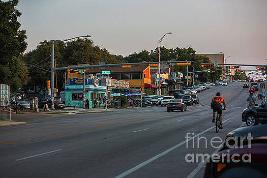Herronstock Prints - A rider on bicycle rides up South Congress Avenue a popular hip neighborhood featuring eclectic shops restaurants and live music venues