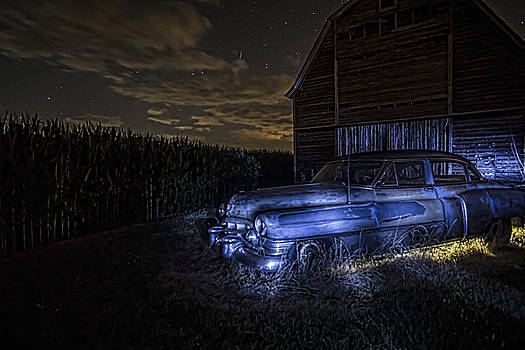 A rusty 50's Cadillac in painted blue and yellow light one starry night by Sven Brogren