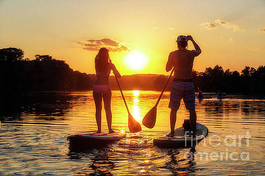 Herronstock Prints - A silhouette of a couple on a stand-up paddle boards SUP at sunset on Lady Bird Lake in Austin Texas