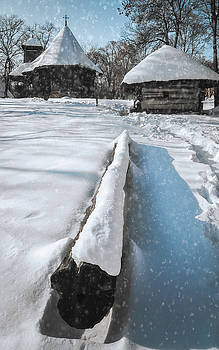 Heavy snow cover in a Romanian village in winter by Daniela Constantinescu