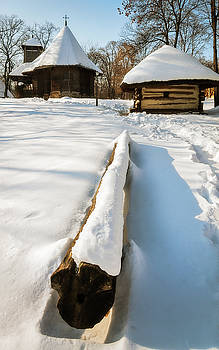 A small wooden church and cottage covered in snow  by Daniela Constantinescu