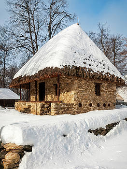 A stone cottage with a thatched roof covered in snow by Daniela Constantinescu
