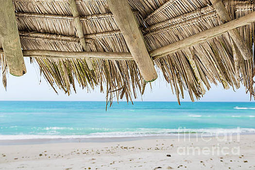 A straw umbrella on a beautiful tropical beach by Mariusz Prusaczyk