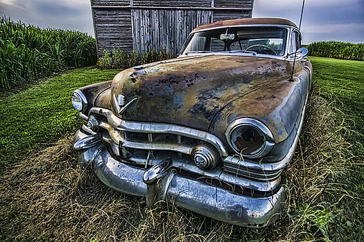 A stylized wide angle look at an old rusty cadillac by a cornfield by Sven Brogren