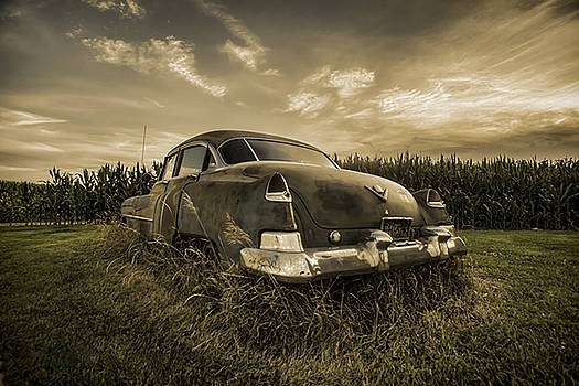 A tinted photo of rusty caddy by a cornfield  by Sven Brogren