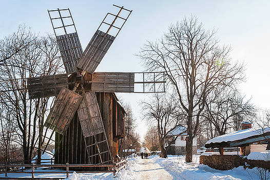 A traditional windmill on a snow-covered street at the Village Museum, Bucharest by Daniela Constantinescu