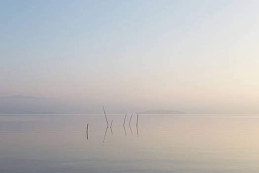 A very minimalistic view of a lake at dawn, with soft light, war by Massimo Discepoli