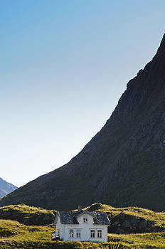 A white house is dwarfed by a steep mountain in northern Norway by Intensivelight