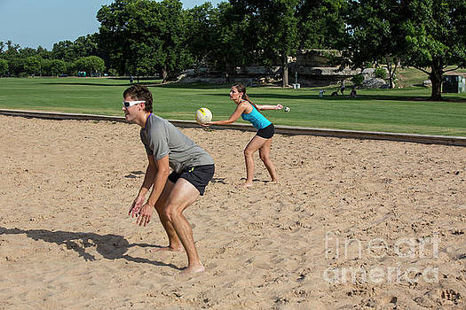 Herronstock Prints - A young attractive female serves volleyball on Zilker Park sand volleyball courts
